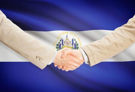 bandera de el salvador: Los hombres de negocios dándose la mano con la bandera de El Salvador en el fondo