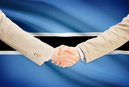botswanan: Businessmen shaking hands with Botswana flag on background