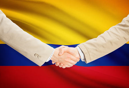 Businessmen shaking hands with Colombia flag on background