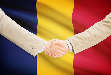 chad flag: Businessmen shaking hands with Chad flag on background