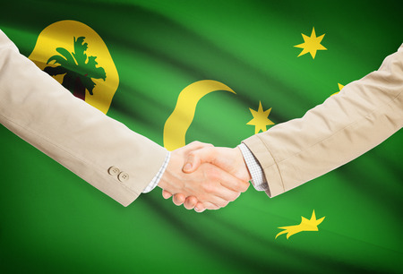 cocos: Businessmen shaking hands with Cocos (Keeling) Islands flag on background Stock Photo
