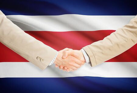 costa rica flag: Businessmen shaking hands with Costa Rica flag on background