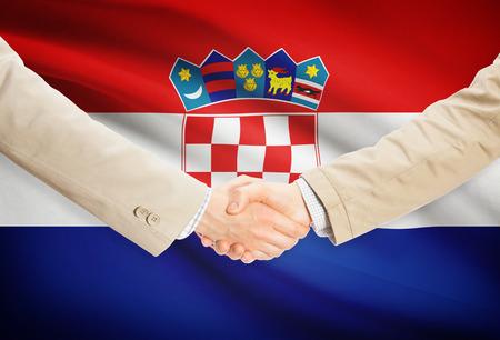bandera croacia: Los hombres de negocios d�ndose la mano con Croacia bandera en el fondo
