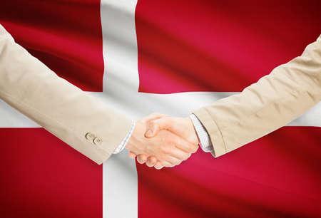 denmark flag: Businessmen shaking hands with Denmark flag on background Stock Photo