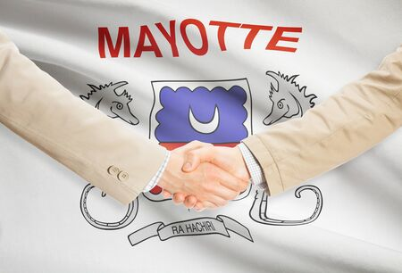 mayotte: Businessmen shaking hands with Mayotte flag on background Stock Photo