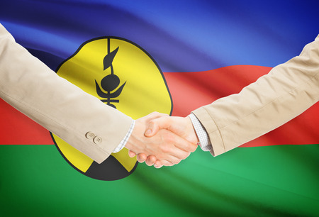 new caledonia: Businessmen shaking hands with New Caledonia flag on background