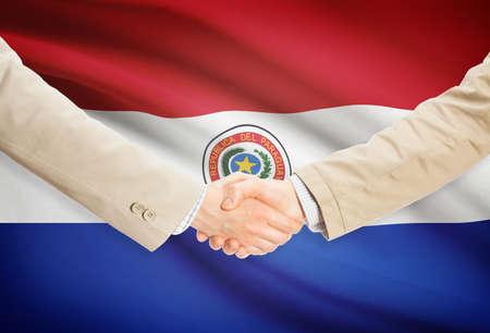 bandera de paraguay: Los hombres de negocios dándose la mano con la bandera de Paraguay en el fondo