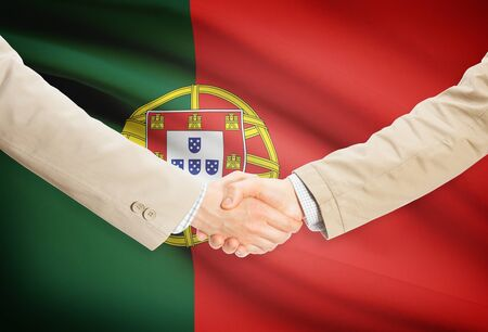 Businessmen shaking hands with Portugal flag on background photo