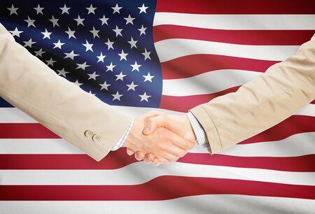 us flag: Businessmen shaking hands with United States flag on background