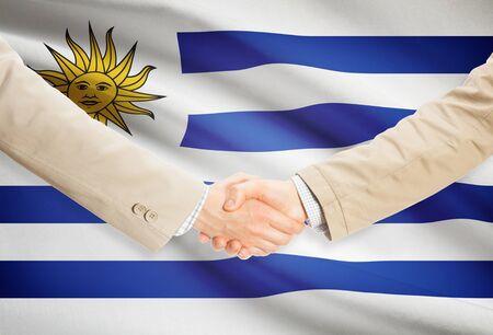 bandera uruguay: Los hombres de negocios dándose la mano con la bandera de Uruguay en el fondo Foto de archivo