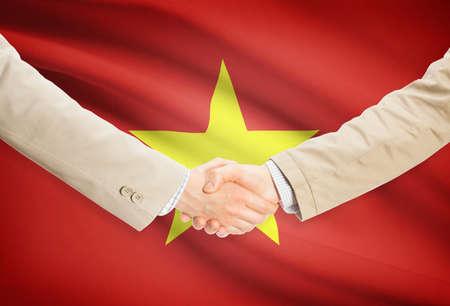 vietnam flag: Businessmen shaking hands with Vietnam flag on background