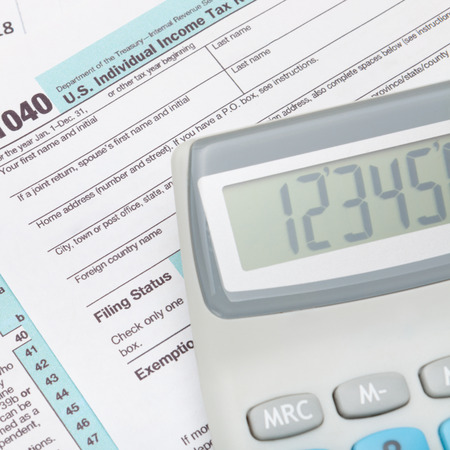 taxable: Calculator over US 1040 Tax Form - close up shot