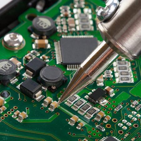 microcircuit: Studio shot of soldering iron with microcircuit Stock Photo