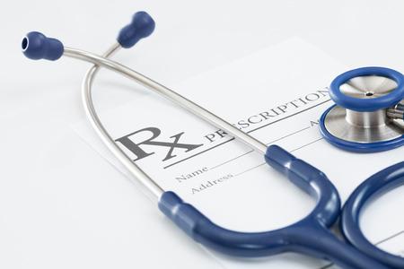obama care: Stethoscope with medical drug prescription on table - studio shot