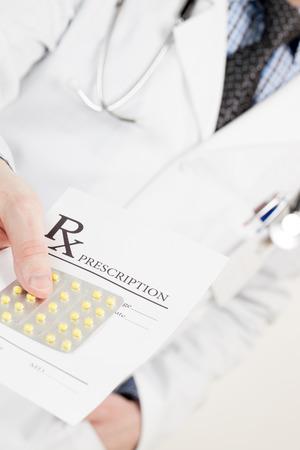 obama care: Medical doctor handing drug prescription and pills - studio shot