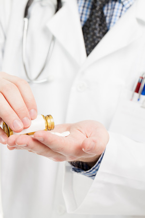 obama care: Medical doctor pouring out pills on his palm - close up shot