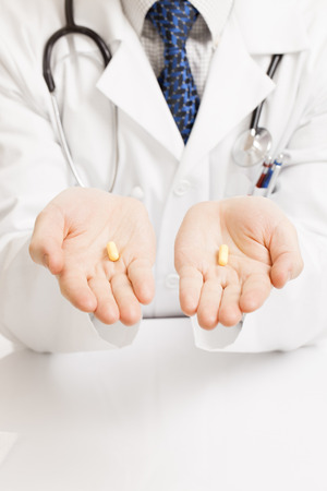 obama care: Doctor holding one pill on each palm - close up shot Stock Photo