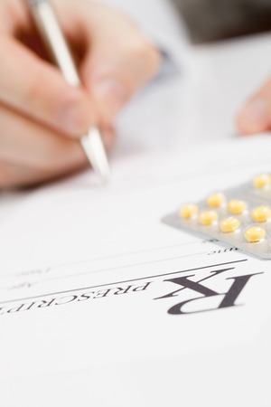 filling out: Doctor filling out drug prescription Stock Photo