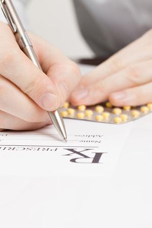 obama: Doctor filling out drug prescription - close up shot Stock Photo