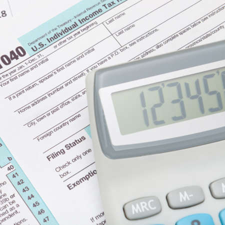 taxable income: Calculator over US 1040 Tax Form - close up shot