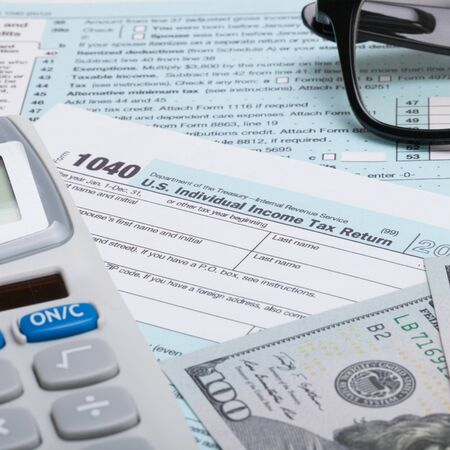 taxable income: US 1040 Tax Form, calculator, glasses and dollars - close up shot