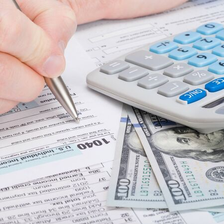 taxable: Taxpayer filling out USA 1040 Tax Form Stock Photo