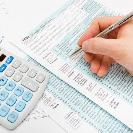 taxable income: Male filling out US 1040 Tax Form - close up shot Stock Photo