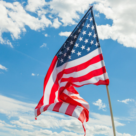 USA flag with clouds on background - close up shot Foto de archivo
