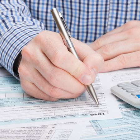 filling out: Taxpayer filling out 1040 Tax Form - close up shot