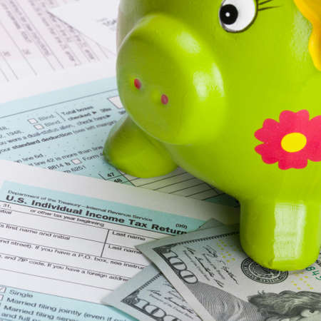 taxable income: Hundred dollars banknote and piggy bank over US tax form - close up shot