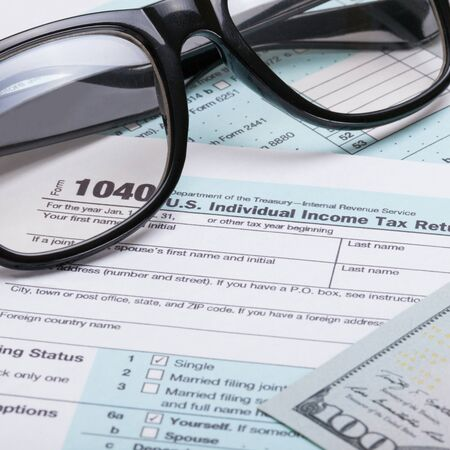 taxable income: US 1040 Tax Form, glasses and dollars - close up studio shot