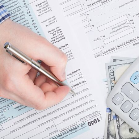 taxable income: Taxpayer filling out USA 1040 Tax Form - close up shot
