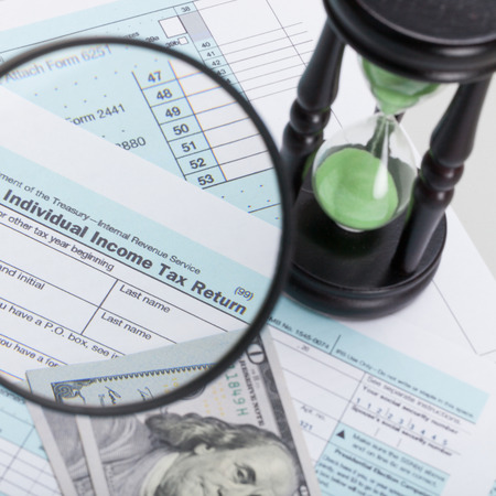 cpa: USA 1040 Tax Form with magnifying glass and hourglass - close up shot Stock Photo