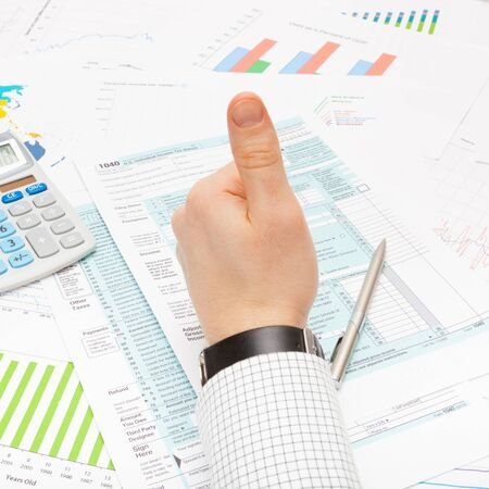 taxable income: Thumb up over 1040 Tax Form - focus on calculator