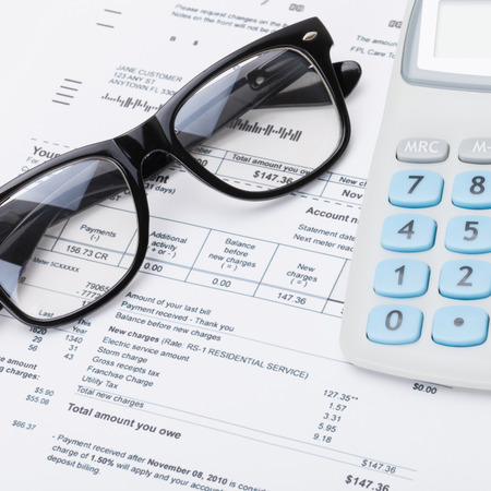 utility payments: Calculator and glasses with utility bill under it - close up studio shot