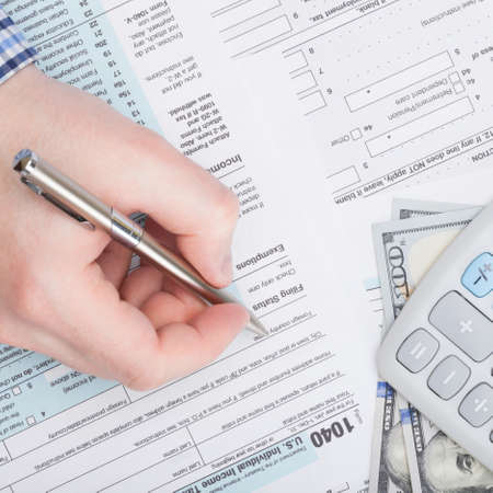 tax form: Taxpayer filling out USA 1040 Tax Form - close up shot