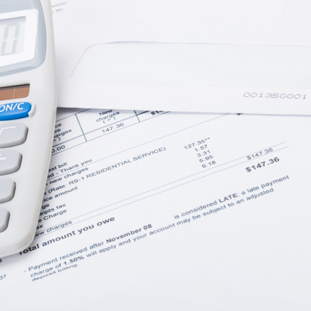 utility payments: Calculator with utility bill under it - close up studio shot Stock Photo