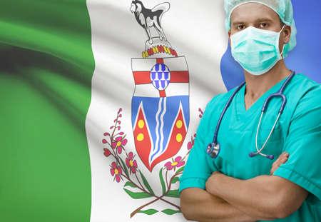 yukon: Surgeon with Canadian province flag on background - Yukon Stock Photo