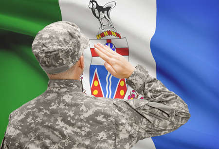 yukon: Soldier saluting to Canadial province flag conceptual series - Yukon