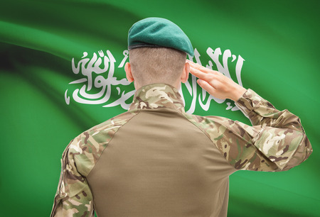 saudi: Soldier in hat facing national flag series - Saudi Arabia