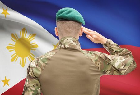 patriotism: Soldier in hat facing national flag series - Philippines Stock Photo