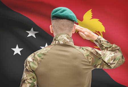 papua new guinea: Soldier in hat facing national flag series - Papua New Guinea Stock Photo