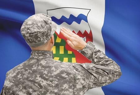 canadian military: Soldier saluting to Canadial province flag conceptual series - Northwest Territories Stock Photo