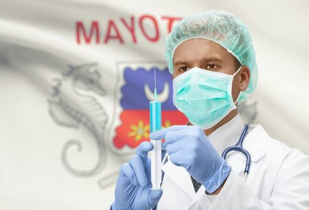 mayotte: Doctor with syringe in hands and flag on background - Mayotte Stock Photo