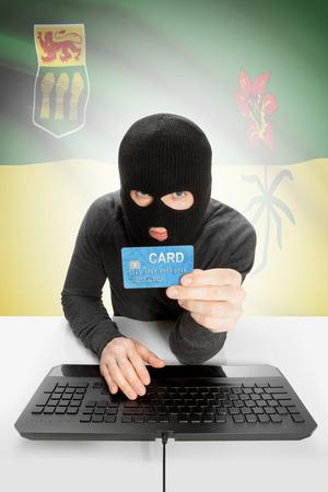 money risk: Hacker holding credit card and Canadian province flag on background - Saskatchewan