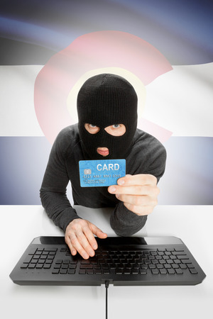 colorado flag: Hacker in black mask with USA state flag on background - Colorado