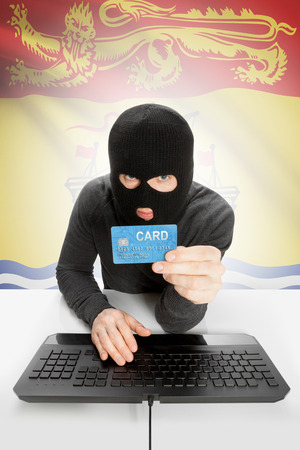 money risk: Hacker holding credit card and Canadian province flag on background - New Brunswick