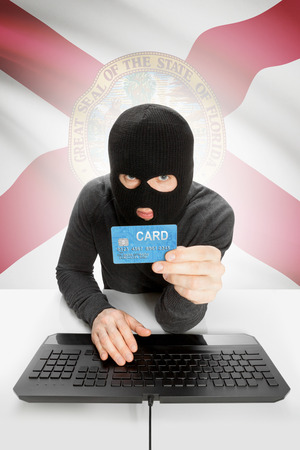 floridian: Hacker in black mask with USA state flag on background - Florida Stock Photo