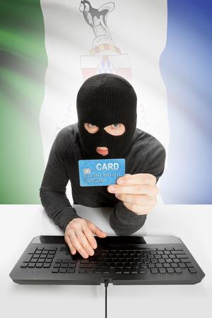 yukon: Hacker holding credit card and Canadian province flag on background - Yukon
