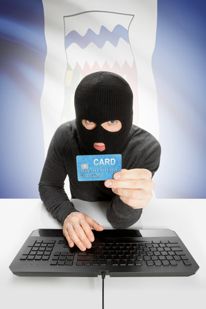 money risk: Hacker holding credit card and Canadian province flag on background - Northwest Territories Stock Photo